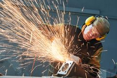 Worker grinding weld seam with grinder machine and sparks Royalty Free Stock Photo