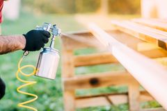 Industrial worker hand using paint gun or spray gun for applying paint on brown timber wood stock photography