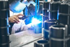 Industrial worker in manufacturing plant grinding to finish a Metal pipe. Industrial Worker at the factory welding closeup Royalty Free Stock Photo