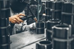 Industrial worker in manufacturing plant grinding to finish a Metal pipe. Industrial Worker at the factory welding closeup Stock Images