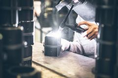 Industrial worker in manufacturing plant grinding to finish a Metal pipe. Industrial Worker at the factory welding closeup Stock Image