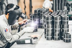 Industrial worker in manufacturing plant grinding to finish a Metal pipe. Industrial Worker at the factory welding closeup Stock Photo
