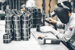 Industrial worker in manufacturing plant grinding to finish a Metal pipe. Industrial Worker at the factory welding closeup Stock Photography