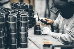 Industrial worker in manufacturing plant grinding to finish a Metal pipe. Industrial Worker at the factory welding closeup Royalty Free Stock Image