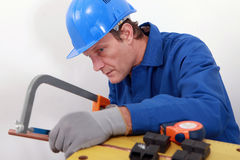 Industrial worker sawing pipe Royalty Free Stock Image