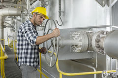 Industrial worker turning large valve Stock Photography
