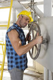 Industrial worker turning large valve Stock Images