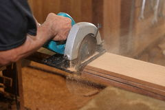 Industrial worker using circular miter saw for cutting wooden boards in carpentry workshop. Industrial worker using circular miter saw for cutting wooden boards Royalty Free Stock Image