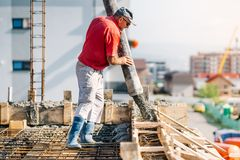 Industrial worker using concrete pipe pump for building house royalty free stock photo