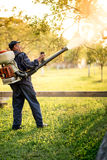 Industrial worker using machine for organic pesticide distribution in fruit orchard Stock Photos