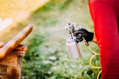 worker using spray gun for painting brown timber royalty free stock photography