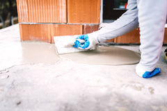 Industrial worker waterproofing part of house exposed to rain Royalty Free Stock Photo