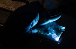 Industrial worker is welding metal pieces. Industrial worker wearing a protective mask is welding two pieces of iron at workshop Royalty Free Stock Images