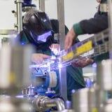 Industrial worker welding in metal factory. Stock Images