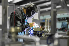 Industrial worker welding in metal factory. Royalty Free Stock Photo