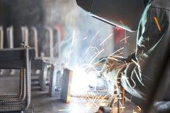 Industrial worker welding. Steel in the dark Stock Image