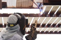 Industrial worker welding steel pipe flange Stock Photos