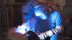 Industrial worker welding steel in protective mask at metalworking factory