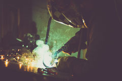 Industrial worker welding on work table, producing smoke, sparks and reflections. Industrial worker welding a loop made of round pipe on work table, producing Royalty Free Stock Images