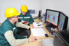 Industrial workers in a control room Royalty Free Stock Images