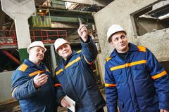 Industrial workers on house building plant. Three industrial engineer chief discussing enterprise development in house-building plant stock photo