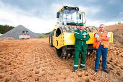 Industrial workers during road works. Industrial workers with soil compactor during road construction works stock photography