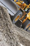 Industrial working. Industrial machine moving gravel on a new road stock image