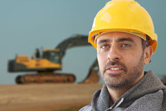 Industrial workman in a hat hat. Handsome young builder or industrial workman in a hat hat or safety helmet against a backdrop showing a large mechanical Royalty Free Stock Photos