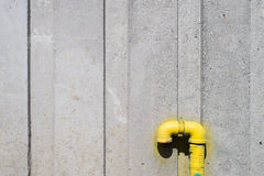 Industrial, yellow pipe on the wall Stock Photos
