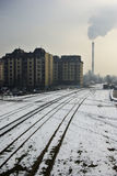 Industrial Zone. Urban winter landscape with train tracks and smoking chimney Royalty Free Stock Image