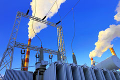 Industrial zone. The electric transformer against factory Royalty Free Stock Photos