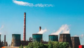 Industrial zone, Power plant with smoking chimneys or manufacturing factory, huge smokestacks with steam as environment pollution Royalty Free Stock Images