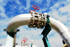 Industrial zone, Steel pipelines and valves against blue sky Stock Images