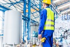 Industriarbetare i fabrik med hjälpmedel Arkivfoton