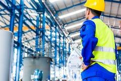 Industriarbetare i fabrik med hjälpmedel Royaltyfri Bild