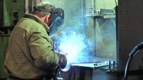 Industriarbetare i skyddande maskering genom att anv?nda den moderna svetsningsmaskinen f?r konstruktion f?r svetsningmetall p? p arkivfilmer