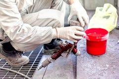 Industriarbetare som förbereder röd målarfärg för att bespruta en bil arkivbilder