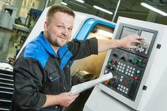 Industriarbetare som fungerar den roterande maskinen för cnc i metall som bearbetar med maskin bransch arkivfoto