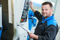 Industriarbetare som fungerar den roterande maskinen för cnc i metall som bearbetar med maskin bransch royaltyfria bilder