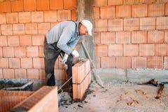 industriarbetare som installerar tegelstenmurverket på innerväggen med murslevspackeln royaltyfri bild