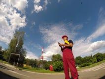 Industriarbetare som ser hans mobiltelefon Arkivfoto