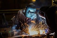 Industriarbetare svetsar applicera den automatiska delen i bilfabrik Arkivbild