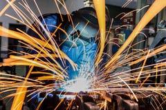 Industriarbetaren svetsar reparationsmetalldelen i bilfabrik Royaltyfri Fotografi