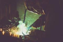 Industriarbetaresvetsning på arbetstabellen och att producera rök, gnistor och reflexioner Royaltyfria Bilder
