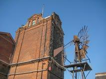 Industribyggnad med en gammal metallisk vindkraftgenerator royaltyfri bild