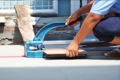 Industribyggnadarbetare som lägger tegelplattan på tegelplattaskäraren Arkivfoton