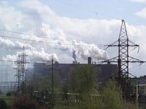 Industribyggnader med att röka lampglas och hög-spänning den över huvudet kraftledningen Arkivfoto
