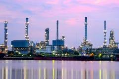 Industrie-Erdölraffinerie, die im Sonnenaufganghimmel arbeitet, Stockbild