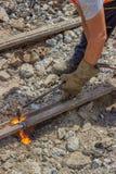 Industriearbeiter, der Bahnen einer alte Tram mit einem oxy-acetylen schneidet Lizenzfreie Stockfotografie