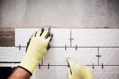 Industriearbeiter, der kleine Keramikfliesen in Badezimmer während der Erneuerungsarbeiten installiert stockbild